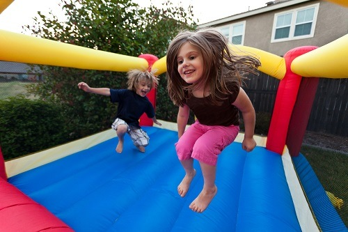 Happy children playing in bounce house.