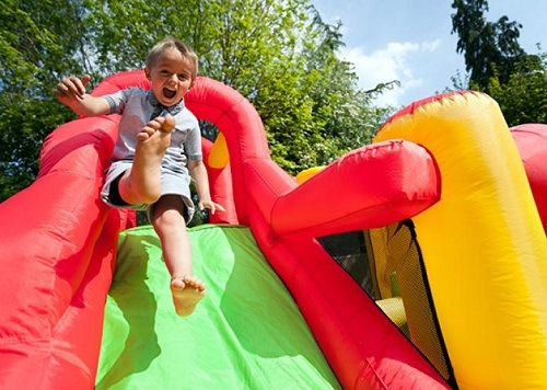 A small boy playing on bouncing castle