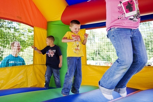 Kids jumping in bounce house.