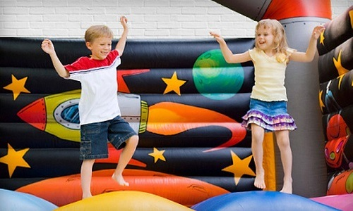 Boy and girl playing in a bouncing house